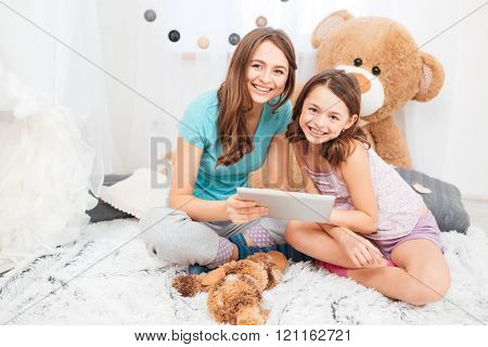 Two charming smiling sisters sitting and using tablet together in children room