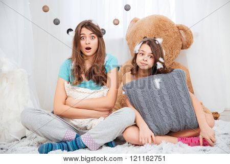Two amazed lovely sisters sitting and hugging pillows at home