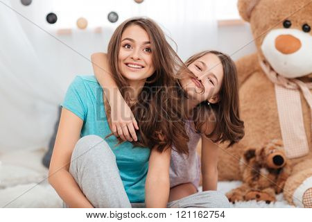 Two cute funny sisters playing and having fun in children room together