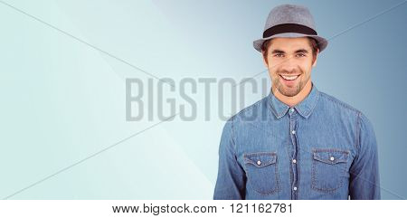 Portrait of happy hipster wearing hat against blue background