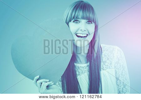 Smiling hipster woman with a big red heart against blue vignette background
