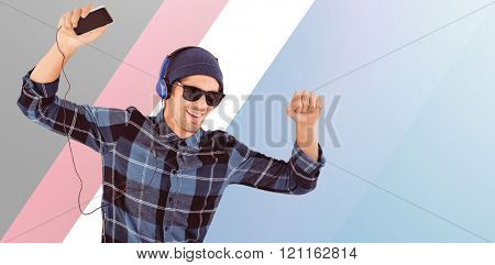 Happy hipster wearing headphones enjoying music against blue vignette background