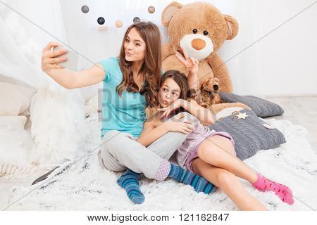 Two charming happy sisters making duck faces and taking selfie in children room
