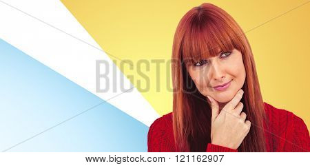 Thoughtful hipster woman looking next to the camera against blue background