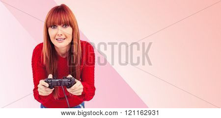 Smiling hipster woman playing video games against pink background