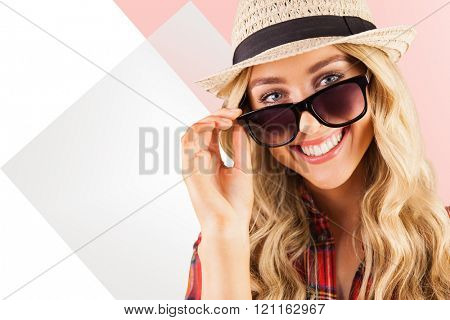 Gorgeous smiling blonde hipster posing with sunglasses against rosa beige and white
