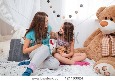 Two pretty smiling sisters sitting in the room and laughing together