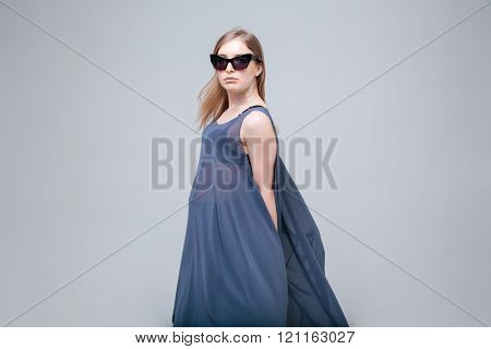 Beautiful woman with sunglasses posing over gray background