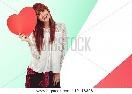 Smiling hipster woman with a big red heart against yellow and blue