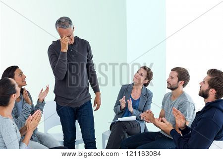 Rehab group applauding delighted man standing up against bright blue
