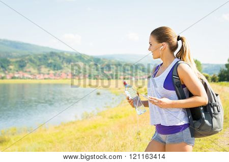 Fit Young Woman Hiking In Nature By The Lake In Summer