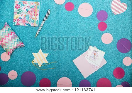 Top view of colorful decorations, notepad, pen and present box on shining turquoise background