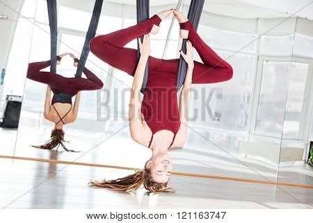 Cheerful attractive young sportswoman doing antigravity yoga exercise in studio