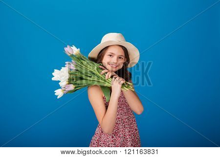 Smiling lovely little girl in hat holding bouquet of flowers on her shoulder over blue background