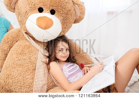Cute smiling girl lying on big plush bear and drawing in children room