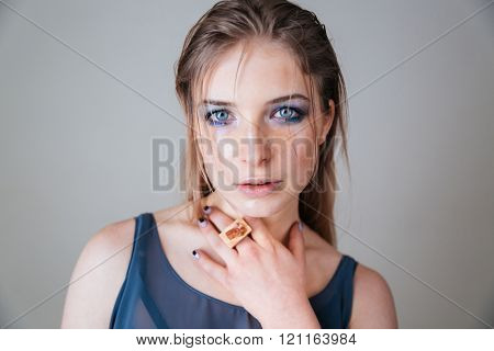 Beauty portrait of a lovely woman with blue eyes looking at camera over gray background