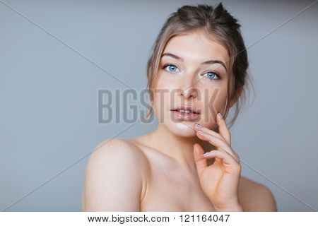 Beauty portrait of a charming woman posing over gray background