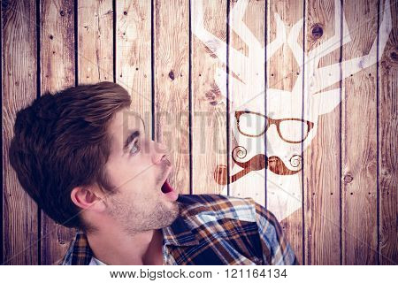 Shocked hipster looking up against wooden planks background