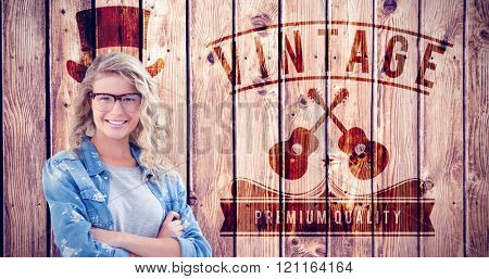 Portrait of smiling businesswoman wearing eyeglasses with arms crossed against wooden planks background