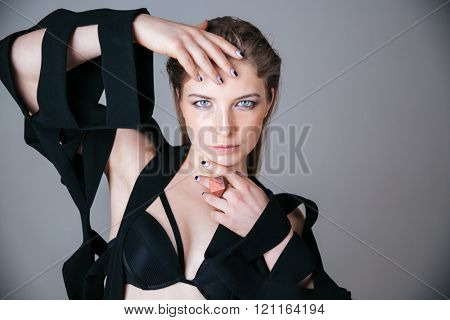 Beautiful woman in fashion cloth posing over gray background