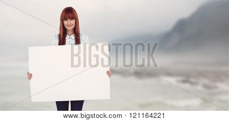 Attractive hipster woman holding white card against ocean against the misty mountains