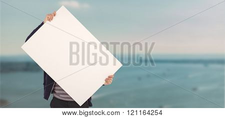 Man holding billboard in front of face against harbour