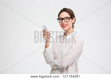 Cheerful attractive young businesswoman in glasses standing and using mobile phone over white background