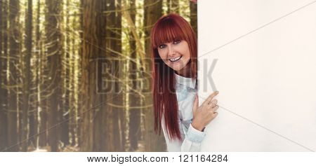 Smiling hipster woman behind a white card against trees in a woods