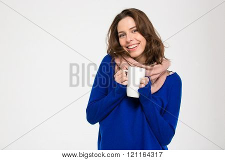 Cheerful attractive young woman in warm pink scarf standing and holding white mug with hot tea over white background