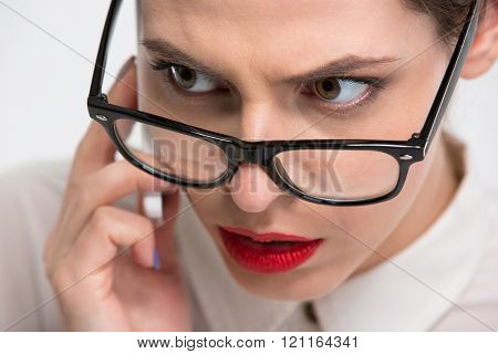 Closeup of serious conentrated young business woman in glasses talking on cell phone over white background