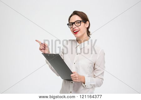 Smiling attractive young businesswoman holding clipboard and pointing away over white background