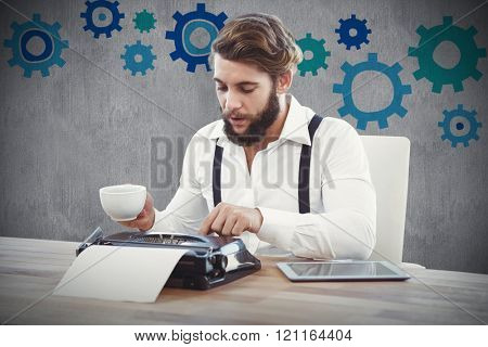 Hipster holding coffee working on typewriter against white and grey background