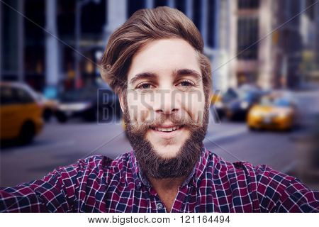 Happy hipster against wooden fence against blurry new york street