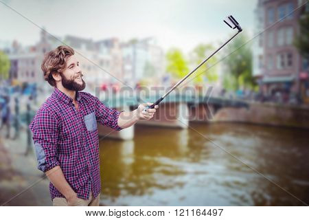 Happy hipster using selfie stick against canal in amsterdam