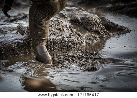Deep muddy water with feet splashing and climbing out of the mud in a race