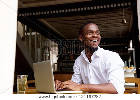 Smiling Black Businessman Working On Laptop At Cafe