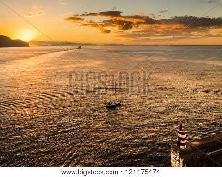 A ferry and a sailing boat leave the port on a golden morning under the safety of the port wall and