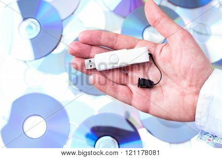Man's hand with pendrive over CD's background. Concept of data storage.