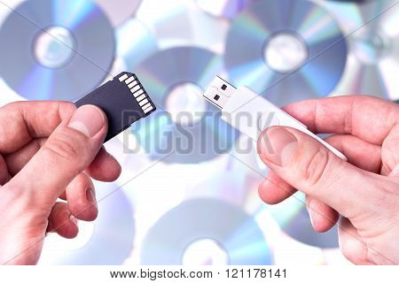 Man's hands with SD card and pendrive over CD's background.