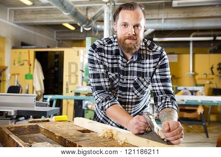 Smiling carpenter work with plane on wood plank in workshop