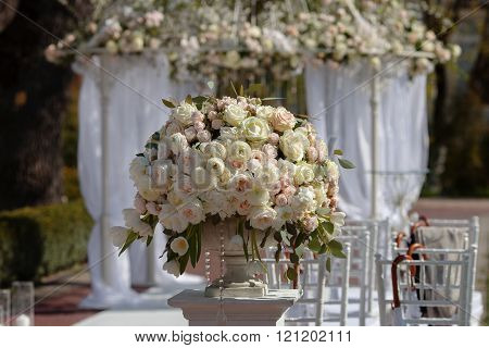 Beautiful bouquet of roses in a vase on a background of a wedding arch. Set up for the wedding ceremony. poster