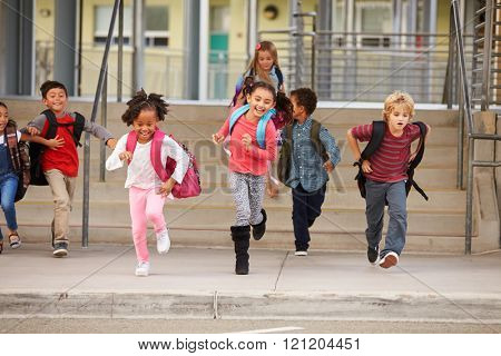 A group of elementary school kids rushing out of school