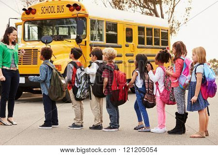 Teacher and a group of elementary school kids at a bus stop