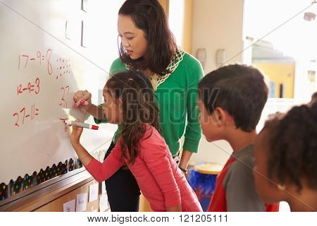 Pupil writing on the board at elementary school maths class