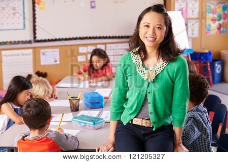 Portrait of teacher in classroom with elementary school kids