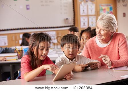 Senior teacher helping elementary school pupils using tablet