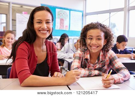 Portrait of teacher with elementary school girl at her desk