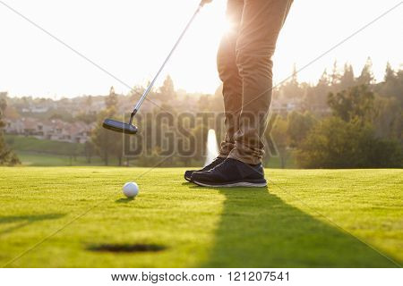 Close Up Of Male Golfer Putting On Green