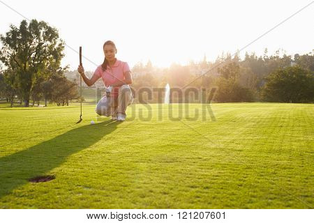 Female Golfer Lining Up Putt On Green