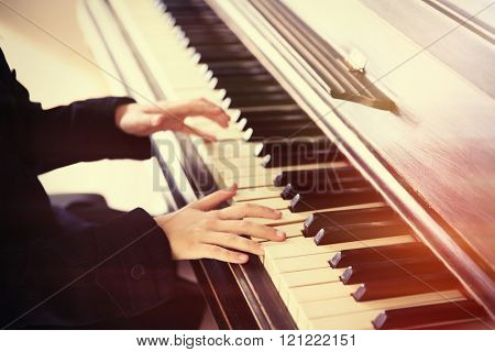 Close up of little girl hands playing piano